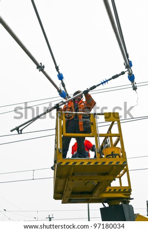 WIESBADEN, GERMANY - FEBRUARY 2:  worker repairs the catenary on February 2,2011 in Wiesbaden, Germany. The equipment is rented by Boehls, the leading rental company in Europe. - stock photo