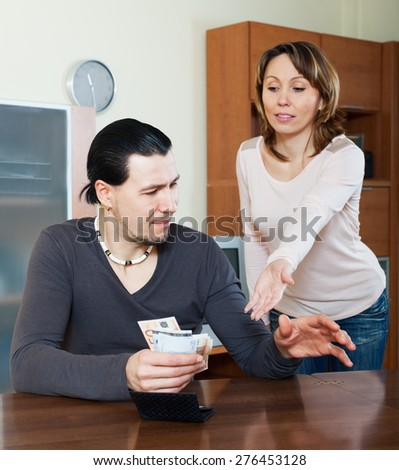 Wife asking for money from her husband for the purchase - stock photo