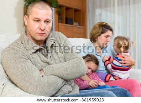Wife can't forgive his husband. Man is sitting on a sofa on the front and his family is sitting behind him. Two crying daughters and a dissapointed wife