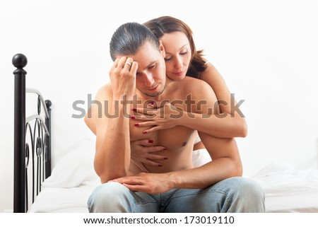 Wife consoling the depressed husband in bedroom at home - stock photo