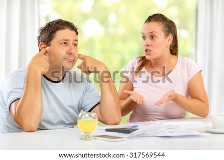 Wife explaining to husband that he must cut on expenses, he is not listening - stock photo