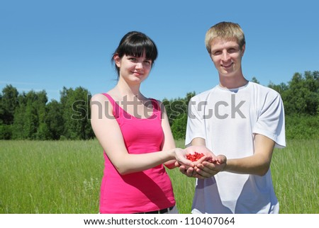 Wife, husband hold berry in hands in field - stock photo