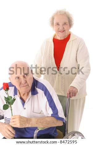 wife pushing elderly husband - stock photo