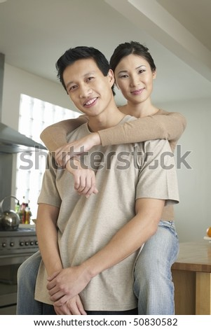 Wife sitting on countertop, arms around standing husband - stock photo