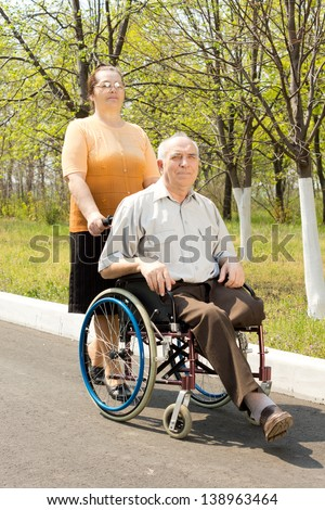 Wife taking her disabled husband for a walk in his wheelchair along a rural road - stock photo