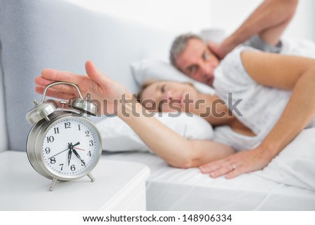Wife turning off alarm clock as husband is covering ears in bedroom at home - stock photo