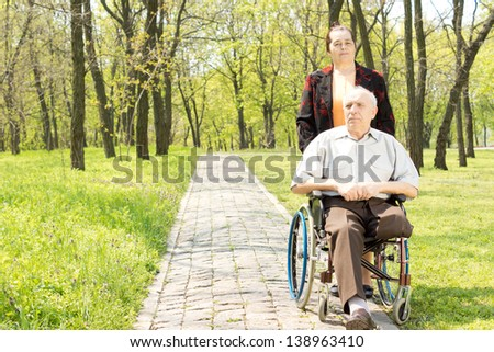Wife walking a disabled man in a wheelchair who has had one leg amputated through a peaceful rural wooded park - stock photo