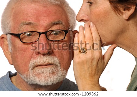 Wife whispers into husband ear - stock photo