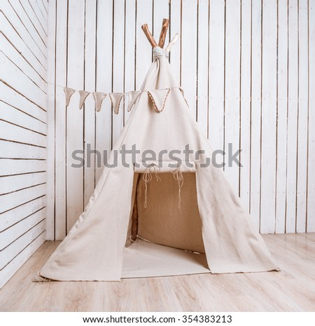 wigwam for children in a room with wooden planked walls