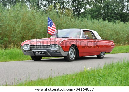 WIJHE, THE NETHERLANDS - SEPTEMBER 4: A Ford 390S from 1961 drives past at the 10th Diekdaegen classic car tour on September 4, 2011 in Wijhe, The Netherlands - stock photo