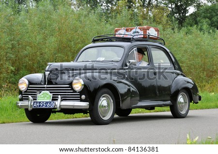 WIJHE, THE NETHERLANDS - SEPTEMBER 4: A Peugeot 203C from 1957 drives past at the 10th Diekdaegen classic car tour on September 4, 2011 in Wijhe, The Netherlands