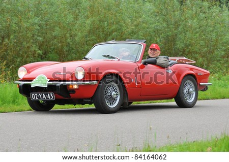 WIJHE, THE NETHERLANDS - SEPTEMBER 4: A Triumph Spitfire Mk4 from 1973 drives past at the 10th Diekdaegen classic car tour on September 4, 2011 in Wijhe, The Netherlands - stock photo