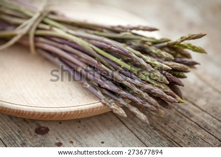 Wild asparagus spears in bunch  on wooden table - stock photo