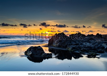 Wild beach and lava rocks at sunset in la Reunion island - stock photo
