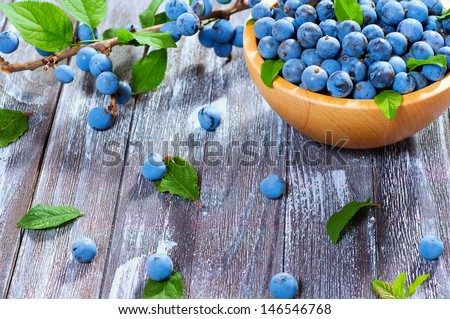 Wild berry thorn on a beautiful wooden background surrounded by green foliage - stock photo