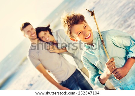 wild boy posing for a photo at the sea while parents look at him - stock photo