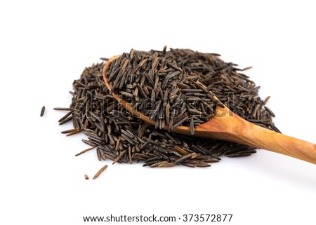 Wild brown rice in wooden spoon and loose over white background