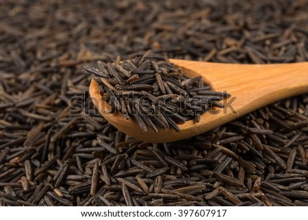 Wild brown rice in wooden spoon close up