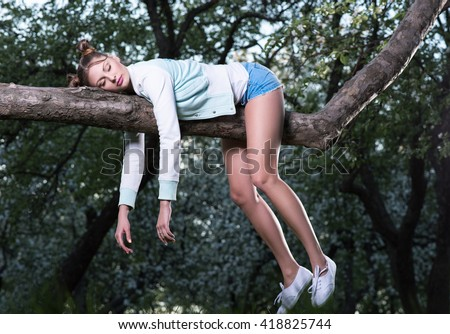 Wild fatigue. Beautiful young woman sleeping on a tree branch. Feet and hands hanging down. Short shorts. Sleepy background - stock photo