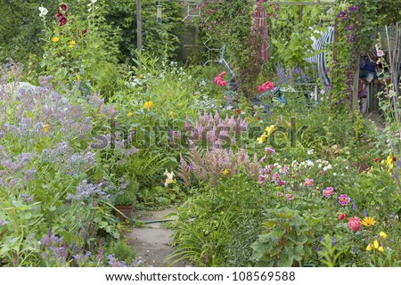 wild flowers and garden path  in a cottage garden. - stock photo