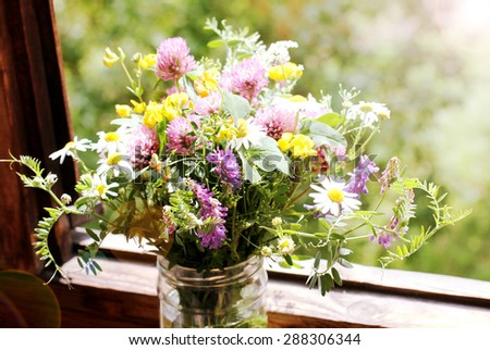 Wild flowers at a window - retro photo