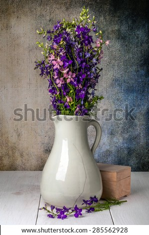 Wild flowers in vase on dark background