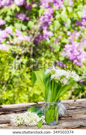 Wild garlic in the glass in front of lilac