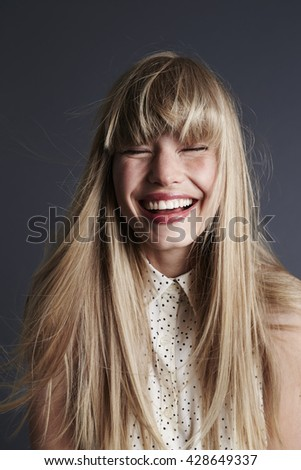 Wild haired and laughing young woman, studio