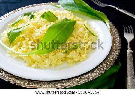 wild leek with saffron basmati rice and lemon om black background - stock photo
