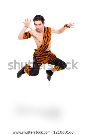 Wild man wearing a tiger skin jumping against isolated white background