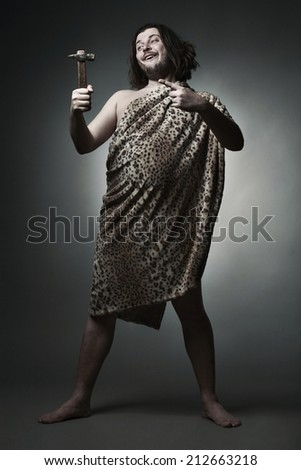 Wild man wearing leopard skin pointing at a hammer, - stock photo