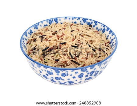 Wild rice, brown basmati and red camargue grains, in a blue and white porcelain bowl with a floral design, isolated on a white background - stock photo