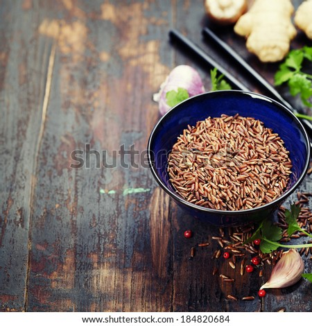 wild rice in ceramic bowl and asian ingredients on wooden background - stock photo