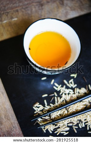 wild rice in ceramic bowl and chopsticks on wooden background - stock photo