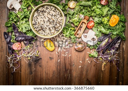 Wild rice with kale and vegetables ingredients for tasty cooking on rustic wooden background, top view.  Vegetarian and healthy food concept. - stock photo