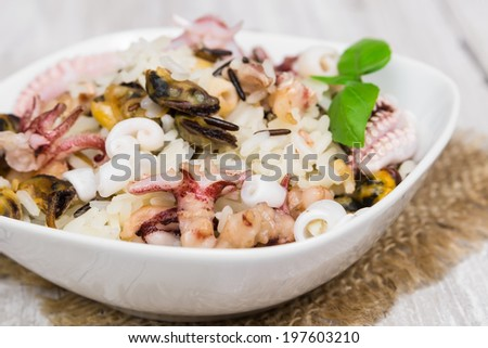 Wild rice with seafood on wooden background