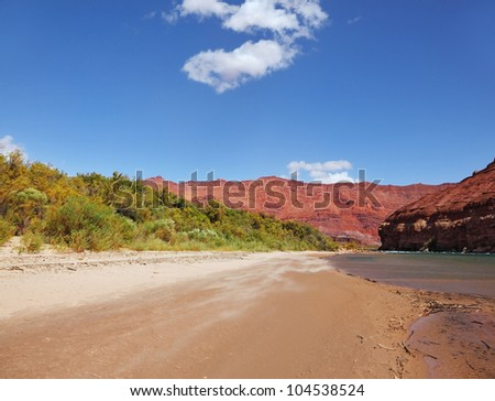 Wild River Colorado. The sandy beach and the steep slope of red sandstone - stock photo
