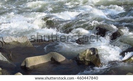 wild river flowing across the stones in the water