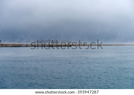 Wild sea during winter. Dramatic scenery with dark clouds and heavy fog above the water.