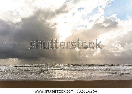 Wild sea waves at sand beach and cloudy sky with sun and sunbeams - stock photo