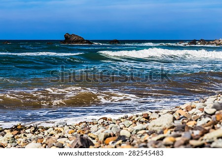 Wild stone beach and rock in water on coast or shore of the Atlantic ocean with waves and sky with clouds and skyline or horizon in Tenerife Canary island, Spain at spring or summer