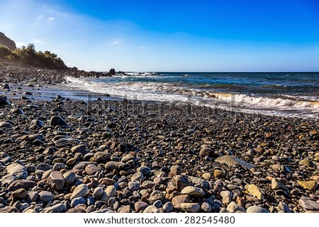 Wild stone beach on coast of the Atlantic ocean with waves and sky with clouds and skyline or horizon in Tenerife Canary island, Spain at spring or summer