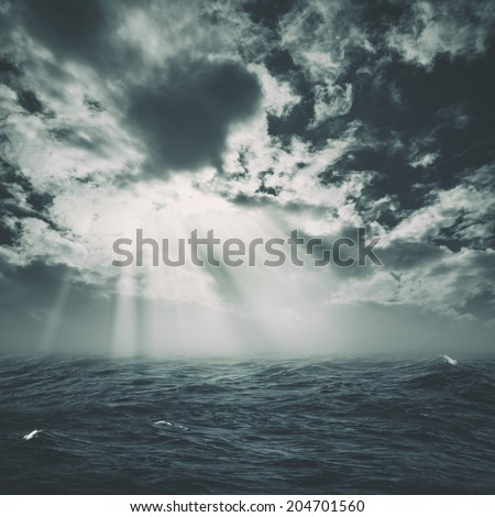wild storm on the sea with sun beam from the cloudy skies - stock photo