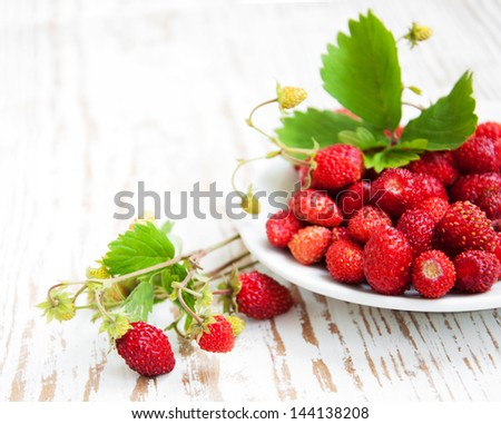 Wild strawberries with leaves in a  plate