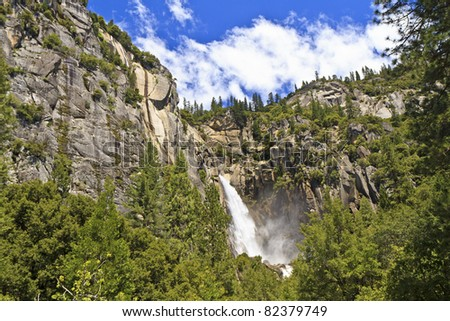 Wildcat Falls plunges between cliffs into forest filled Yosemite Valley in Yosemite National Park, California