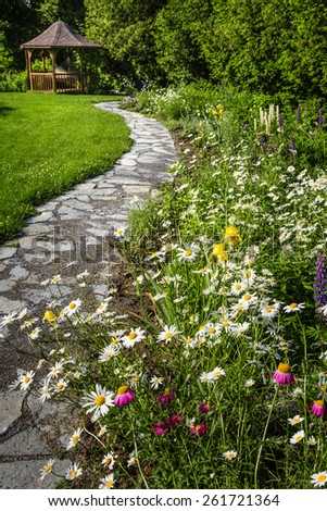Wildflower garden with paved path leading to gazebo and blooming daisies - stock photo