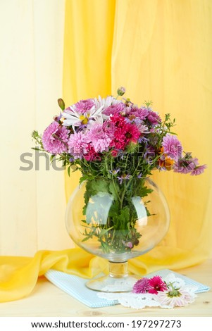 Wildflowers in glass vase on table on yellow fabric background