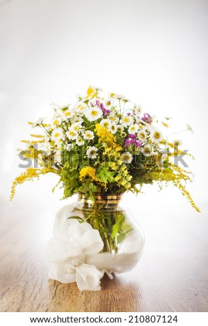 Wildflowers in glass vase with bow on white background - stock photo