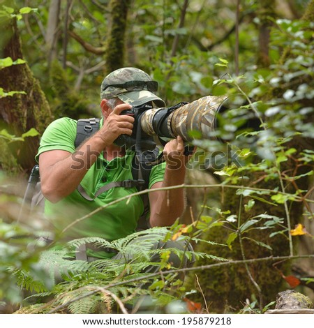 wildlife photographer outdoor in the woods - stock photo