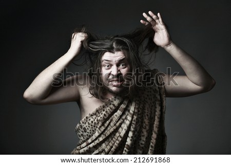 Wildman in leopard skin touch hair - stock photo